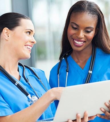 smiling nurses looking at laptop