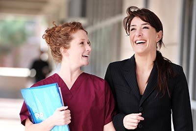 Female Doctor and Nurse laughing in Hospital Corridor.